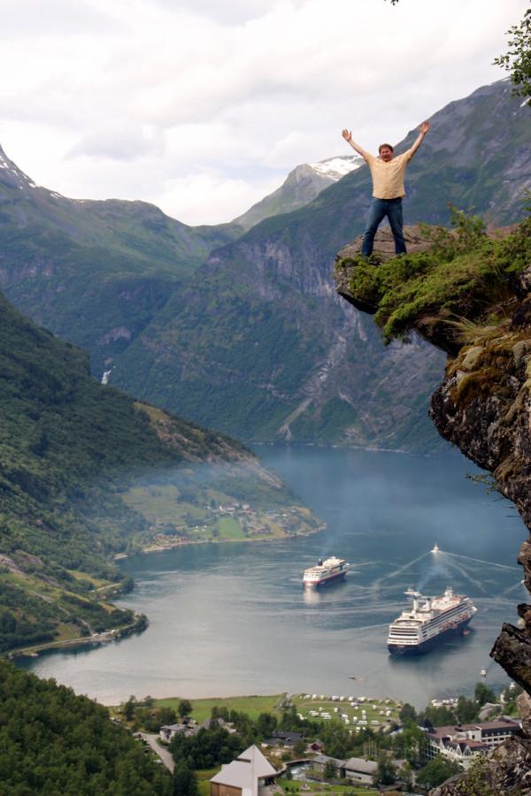 Человек стоит на скале над гейрангер фьордом