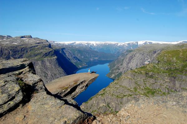 Человек сидит на краю скалы Трольтунга язык тролля в Норвегии